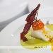 -Baccalà infornato su crema di fave novelle, pomodoro confit, vela di peperone crusco IGP di Senise e olio alla polvere di peperone secco.